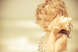 Happy child listen to seashell at the beach